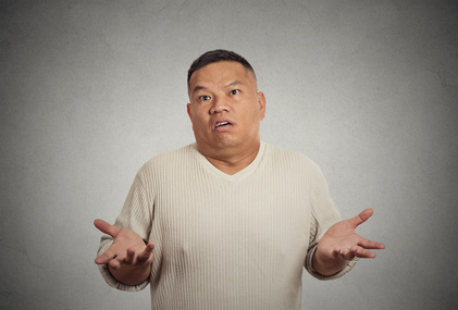 Closeup portrait dumb clueless young man arms out asking why what's problem who cares so what I don't know isolated grey wall background. Negative human emotion facial expression feeling body language