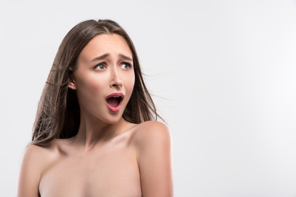 Young girl is very scared. She is standing with naked shoulders and shouting. Isolated and copy space in right side