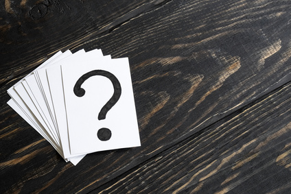 Question mark heap on table concept for confusion, question or solution on wooden background on the left
