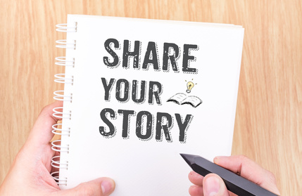 Share your story word on white ring binder notebook with hand holding pencil on wood table,Business concept.